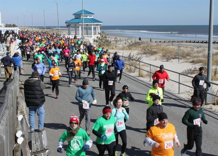 People running a marathon alongside the shore