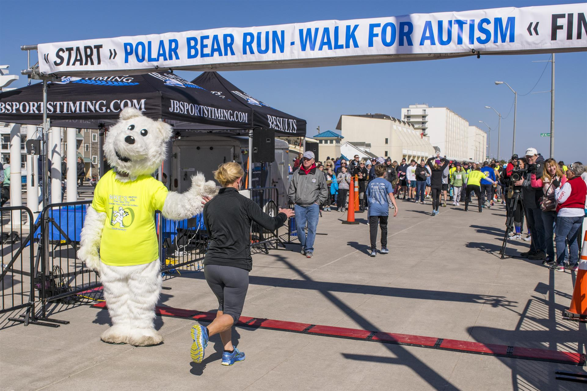 polar bear mascot high fiving a runner