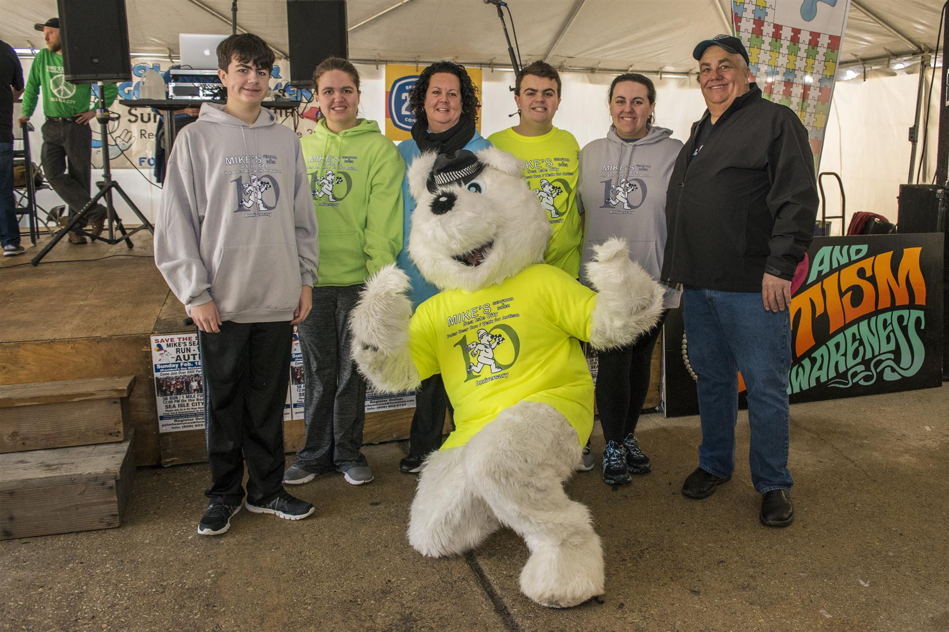 a mascot in a polar berar suit posing with rac runners