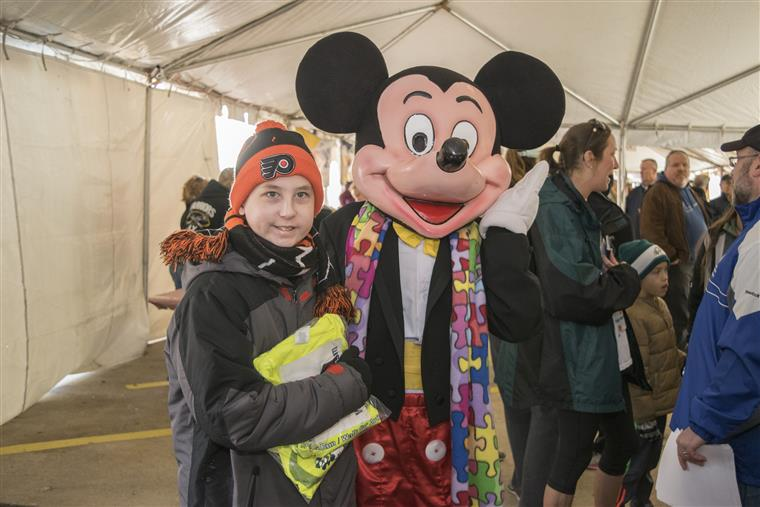 child posing with mickey mouse mascot wearing autism puzzle piece scarf at the race event inside the tent