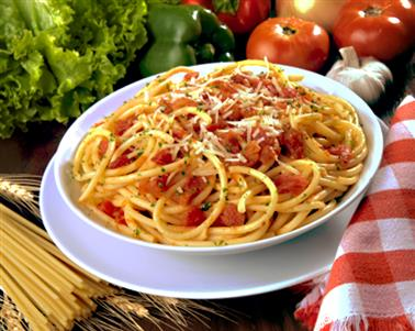 A pasta dish with red sauce beside fresh vegetables