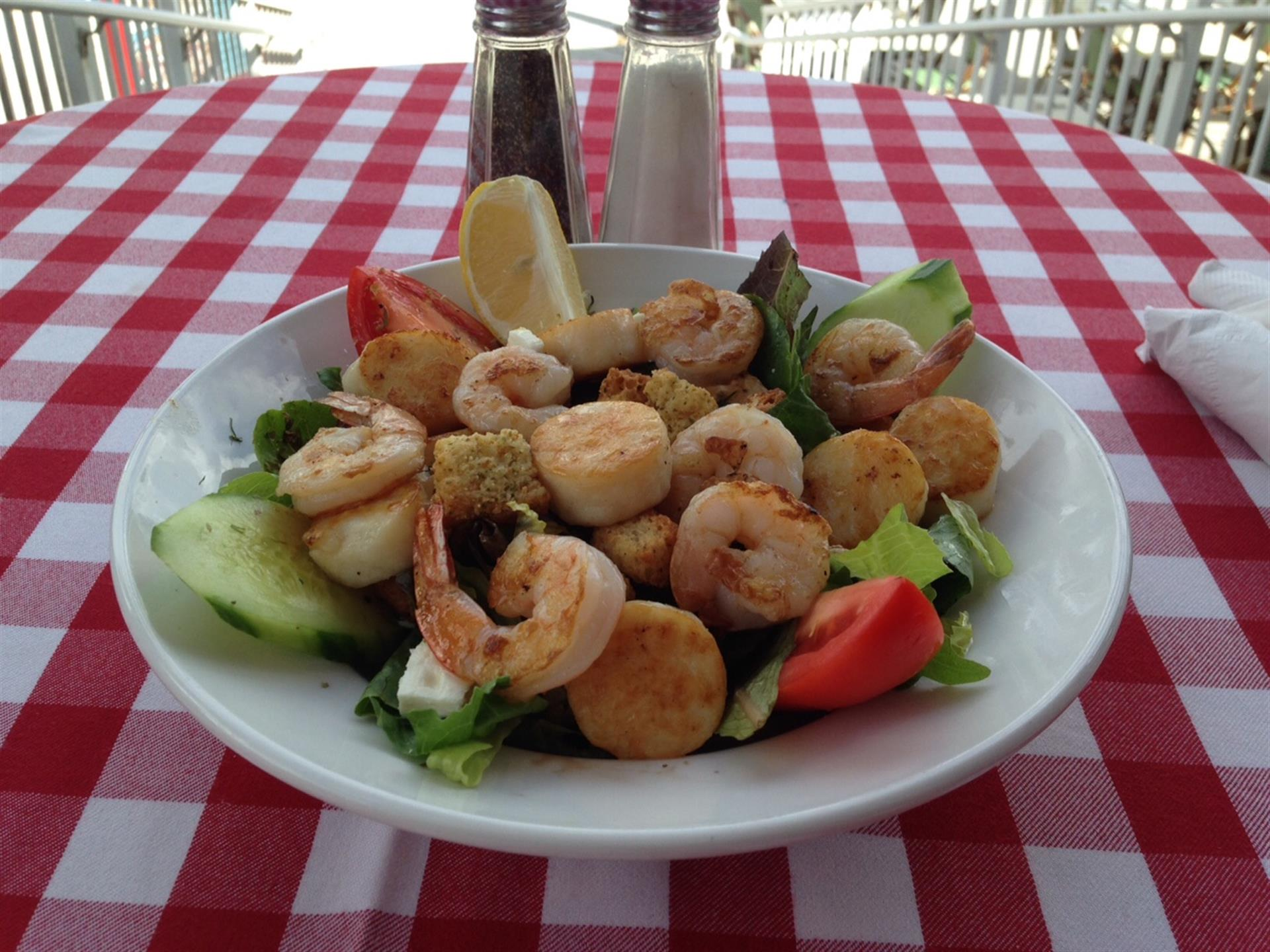 Salad with mixed greens, sliced tomato, cucumber, shrimps, scallops and lemon