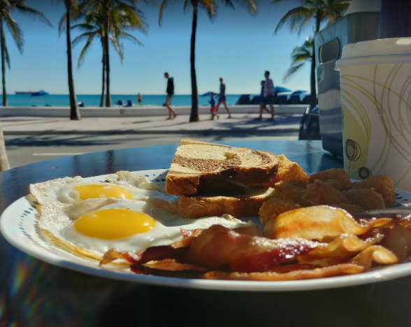 two eggs sunny-side up with bacon and rye toast