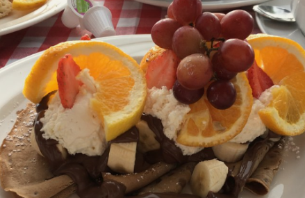 chocolate crepes topped with cream, strawberries, orange slices and grapes