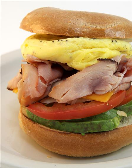 breakfast bagel with eggs, ham, cheese, lettuce and avocado