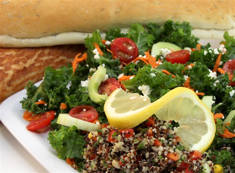 quinoa salad with kale, vegetables and a lemon wedge
