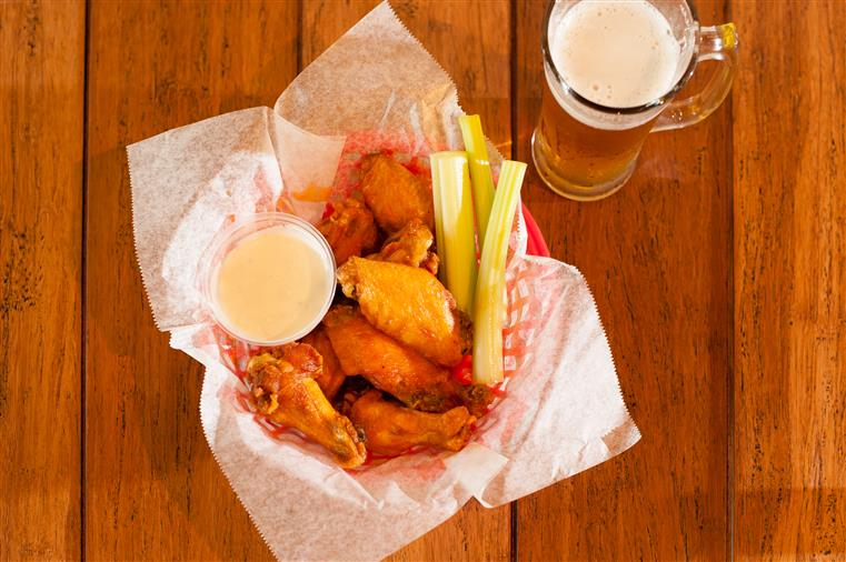Basket of chicken wings with celery and ranch dressing next to full beer glass on wooden table.