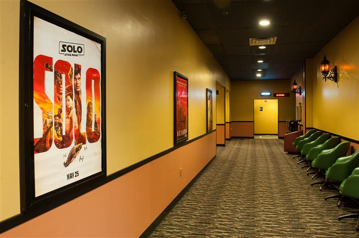 outside hallway of theater with movie posters on the wall