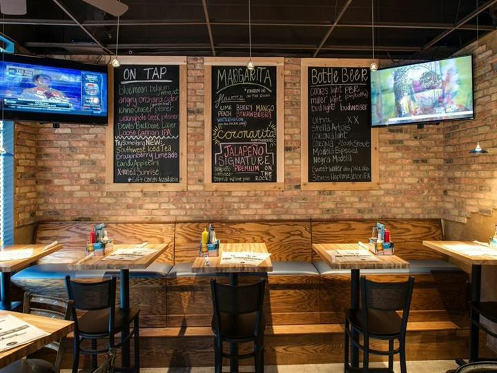 interior dining area with booths, tables and chairs with chalkboard specials hanging from the ceiling