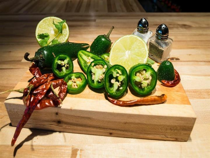 sliced jalapenos and lime wedges on a cutting board