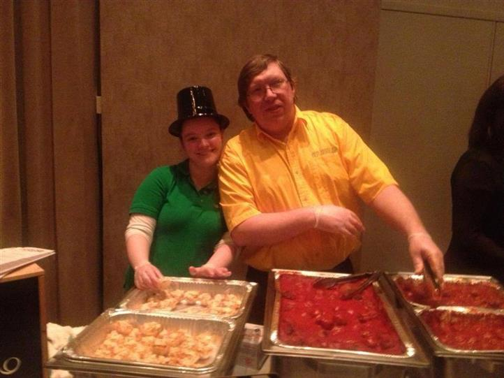 two people posing with serving trays