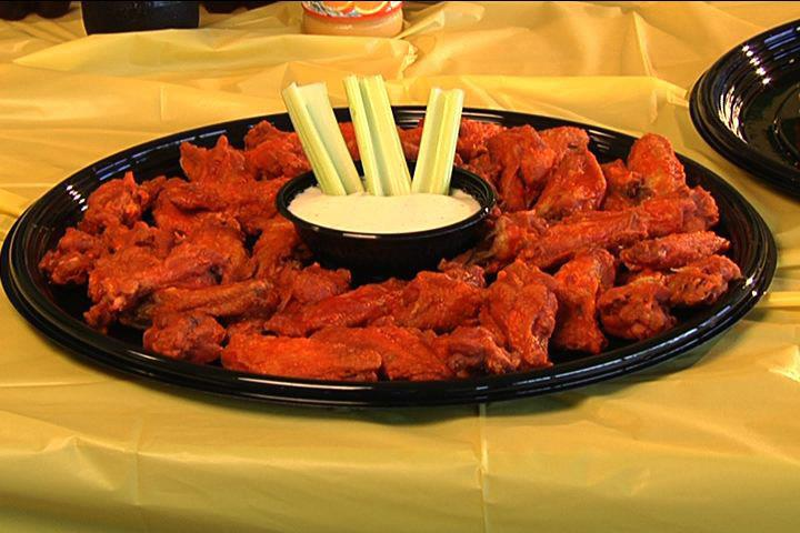 plate of hot wings with ranch and celery