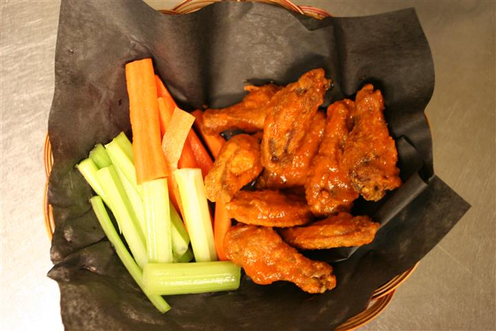 basket of buffalo wings and celery sticks