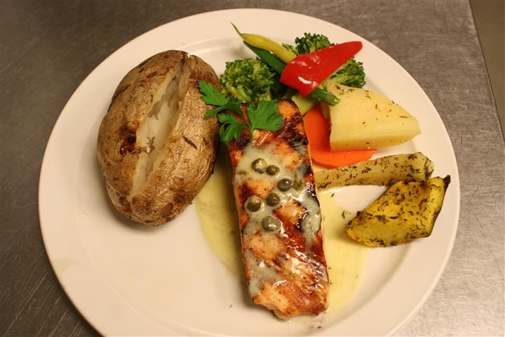 salmon fillet with a baked potato and vegetables