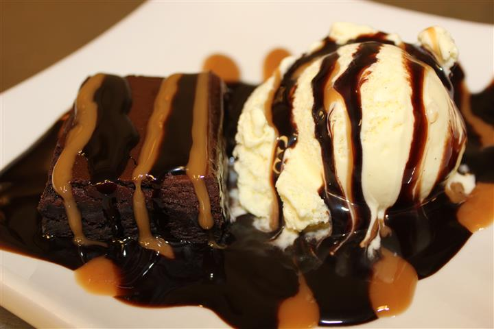 chocolate brownie with a scoop of ice cream on the side