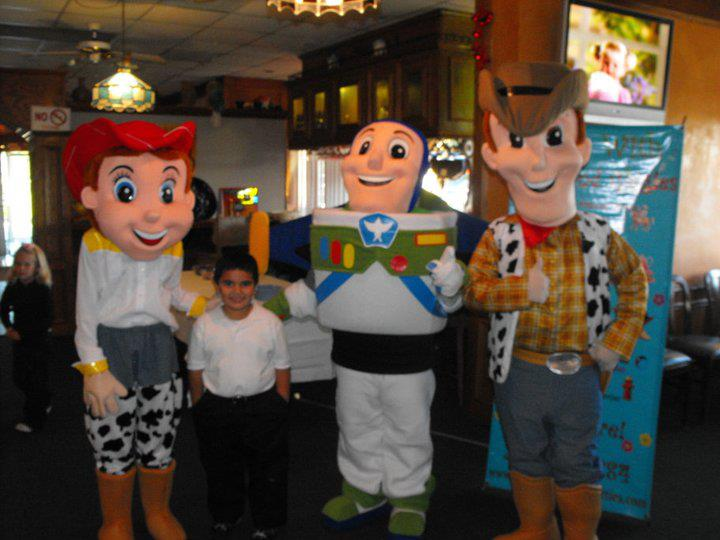 young boy posing for photo with jessie, buzz lightyear, and woody from toy story mascots