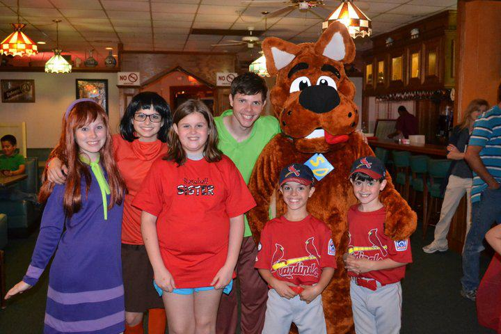 guest posing for photo with scooby doo mascot