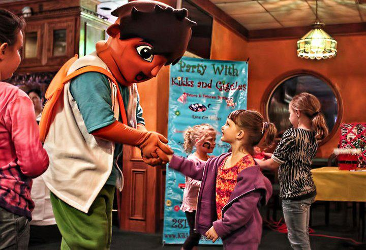 young girl shaking hands with children show character mascot