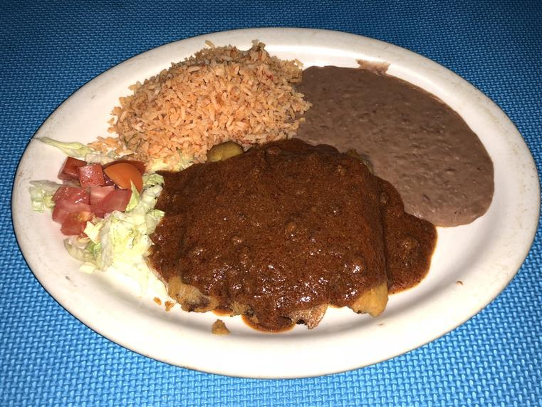 side salad, rice, refried beans, and meat with brown sauce on top
