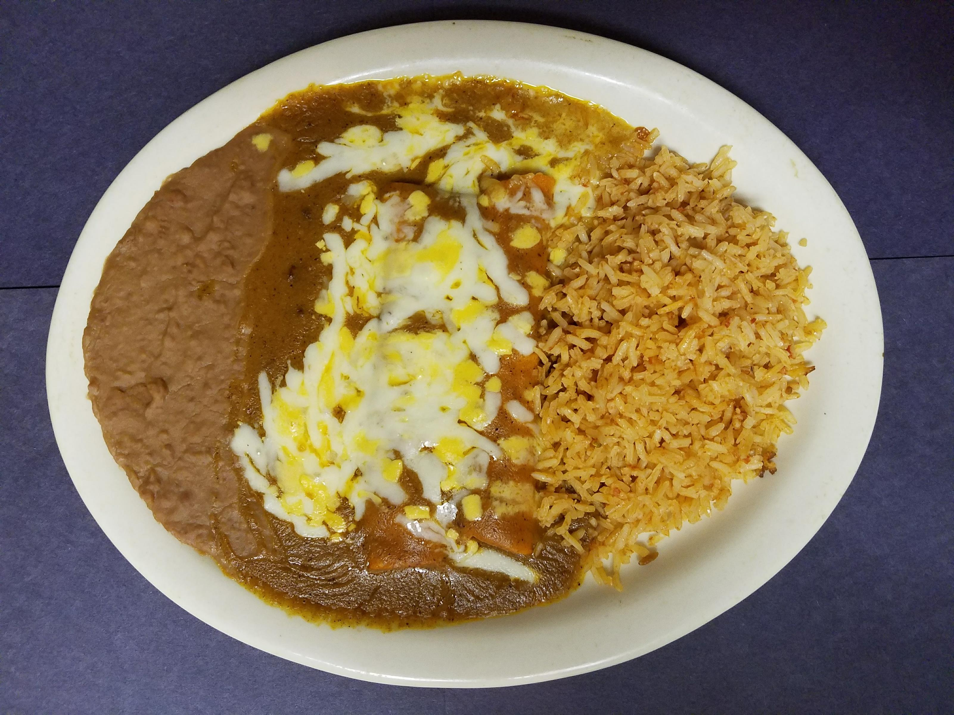 plate of refried beans, chicken with cheese on top, and rice