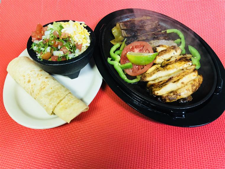 grilled chicken, tomato, grilled steak and peppers on a plate with tortilla and salad on the side