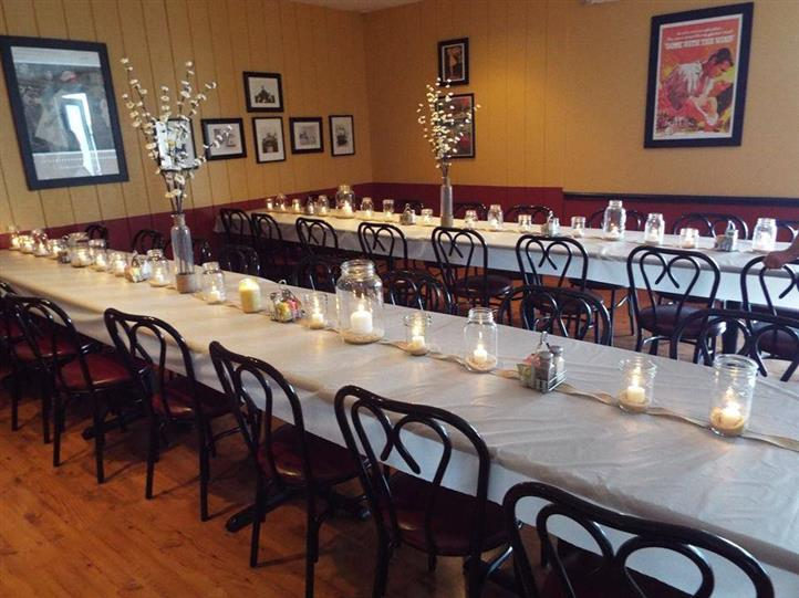 Long tables with white table cloths, candles and whte flowers