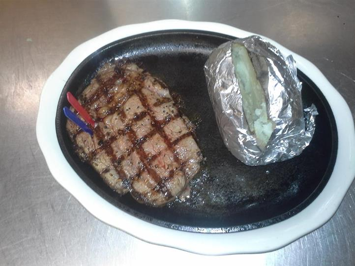 Grilled meat served with a baked potato