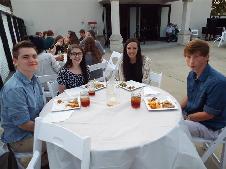 Four teenagers while eating at a rounded tabled posing for photo