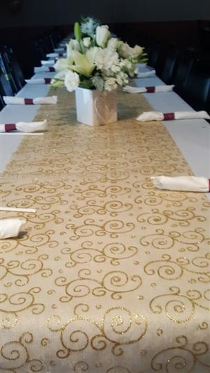 Long tables with golden runner, white nupkins in red nupkin rings