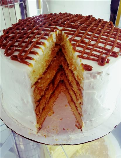 A four level cake with white frosting and milk chocolate