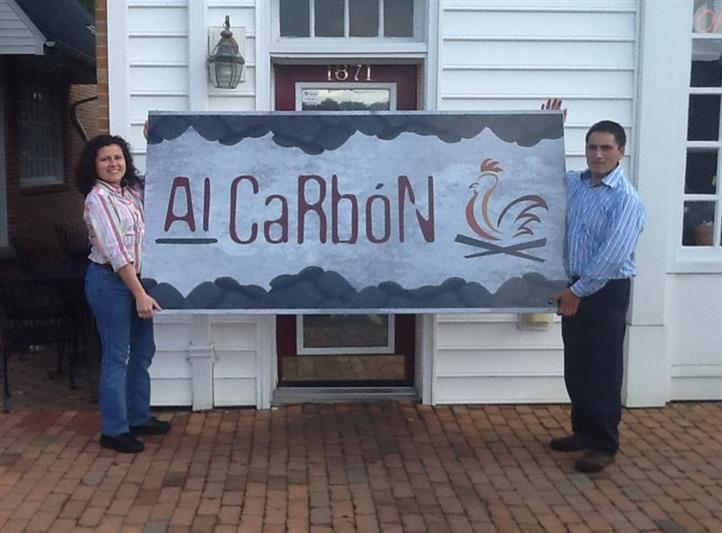 two people holding an Al Carbon sign