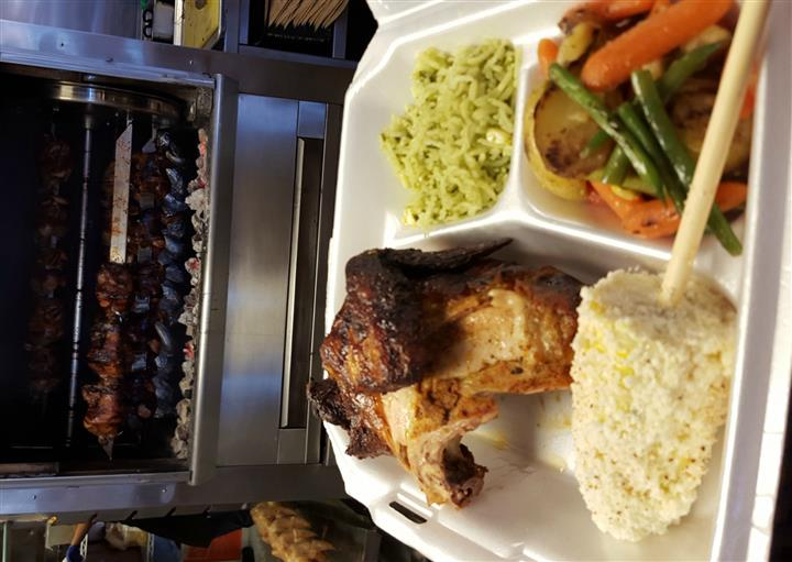 a tray with chicken and various sides