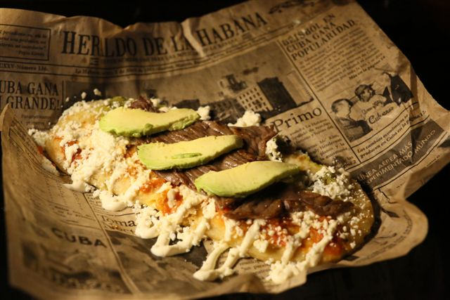 huaraches topped with cheese and avocado