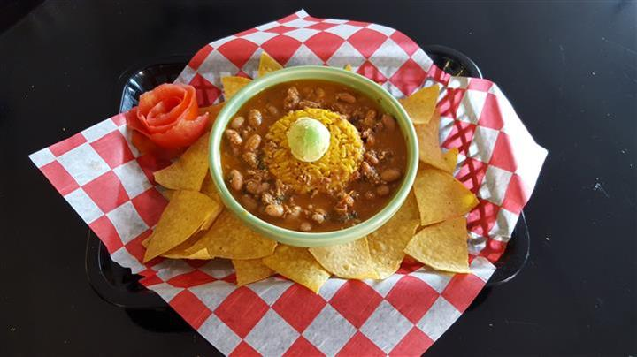 bean and rice soup in a bowl, with tortilla chip son the side