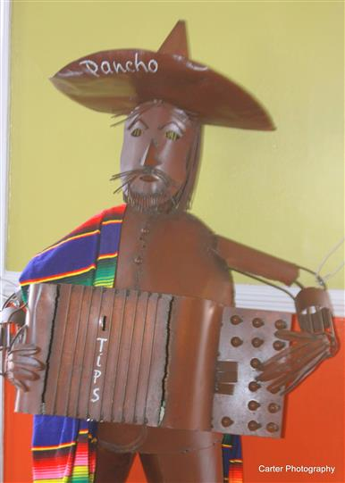 a copper statue of a man wearing a sombraro and playing an accordion