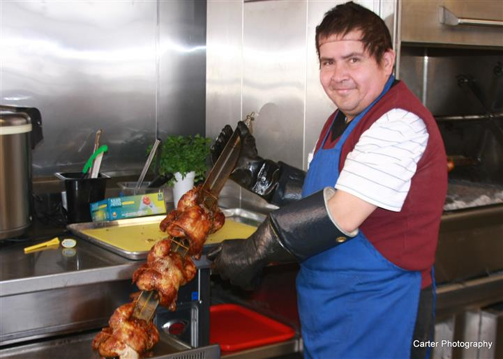 a cook holding a rotisserie skewer with several chickens on it