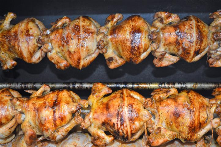 several chickens roasting on a rotisserie