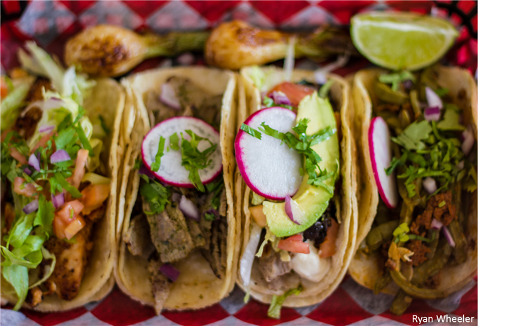 several tacos with meat and vegetables