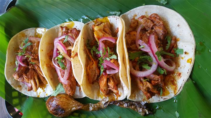 several soft tacos loaded with chicken and beef topped with onions and lettuce