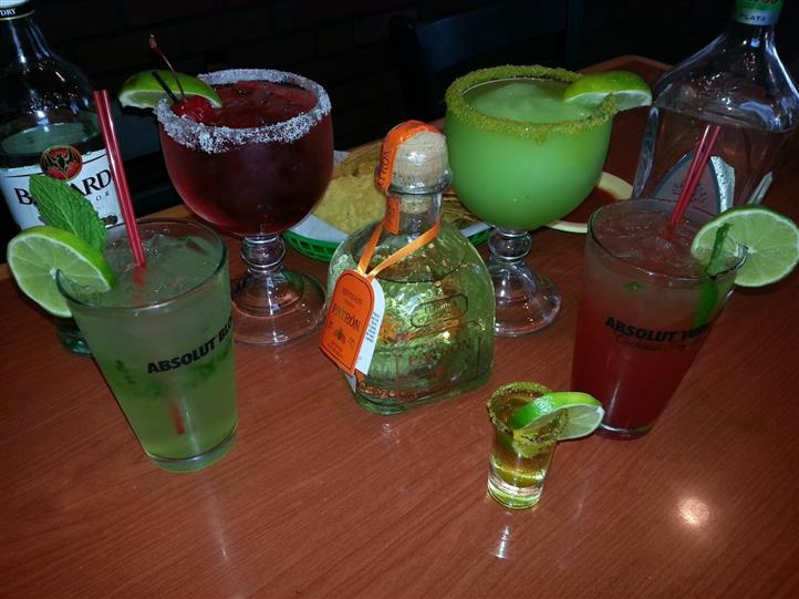 various mixed drinks on a table with a shot glass