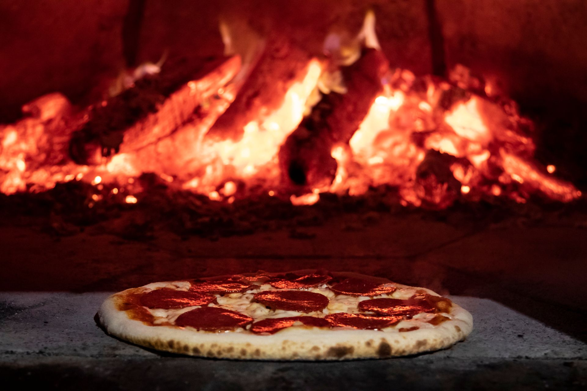 Pepperoni pizza resting in front of a wood burning oven