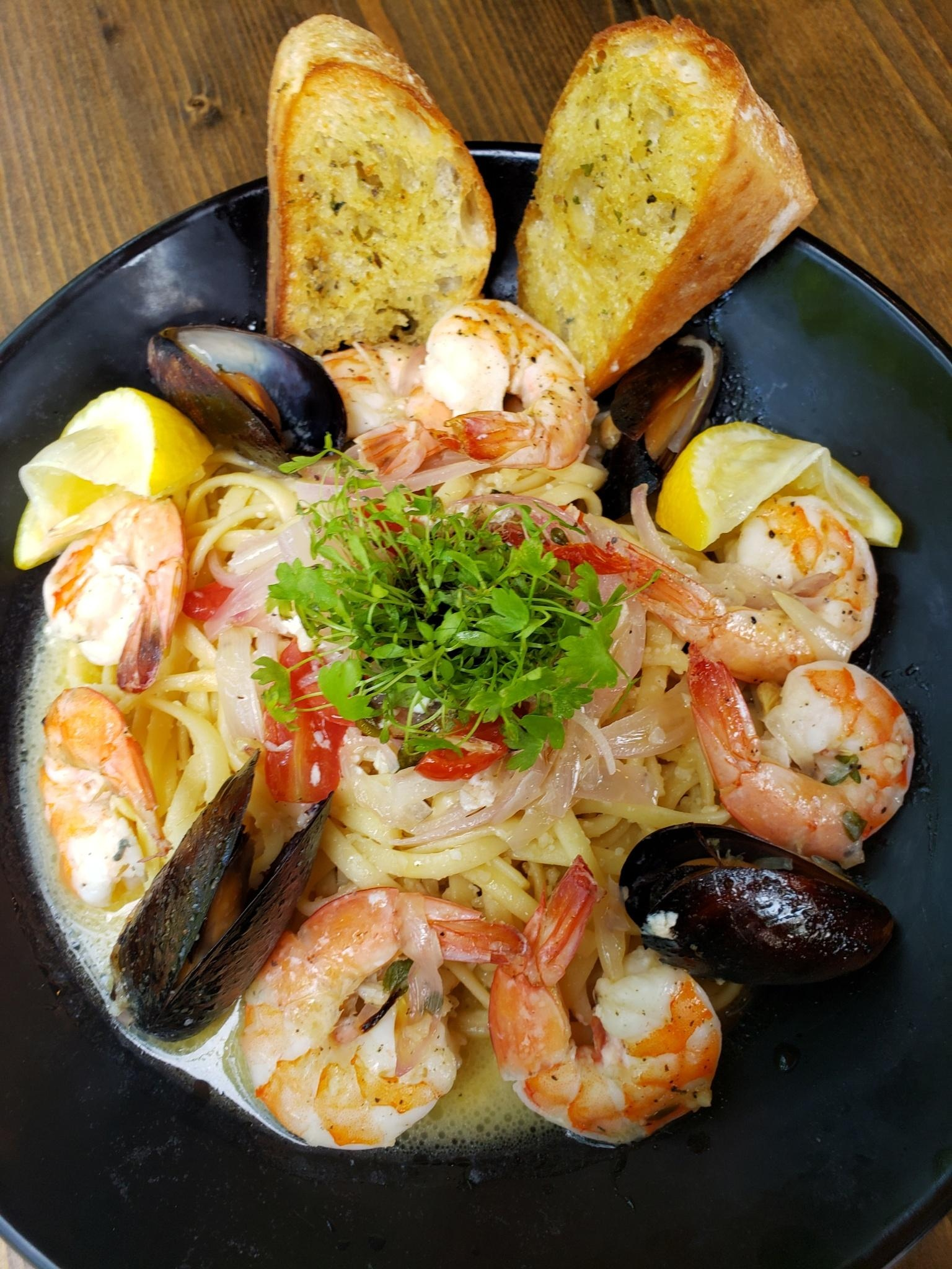 Spaghetti with toasted garlic bread slices, mussels and shrimp
