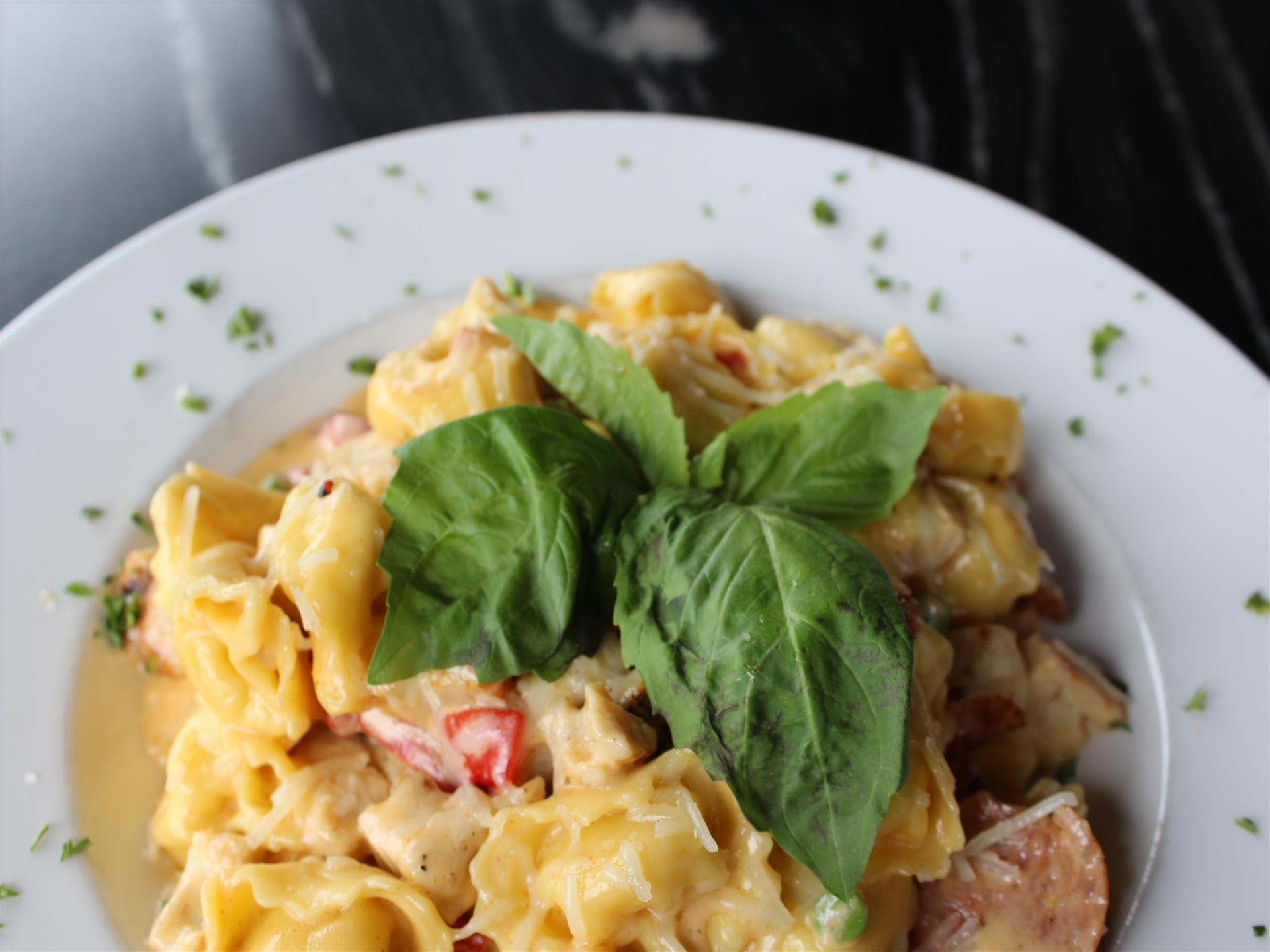 tortellini in a creamy sauce with sausage and peppers