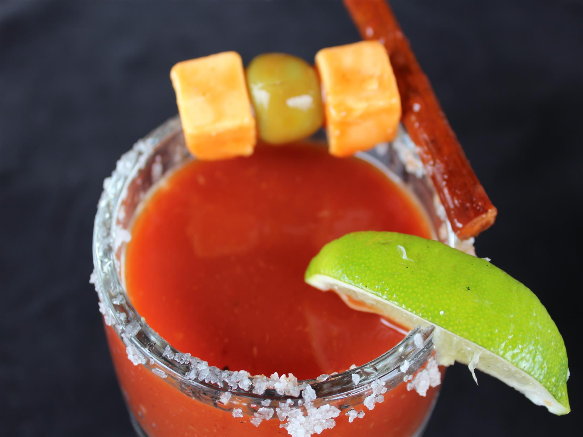 bloody mary topped with lime, salt, olives, beef jerky and cheese