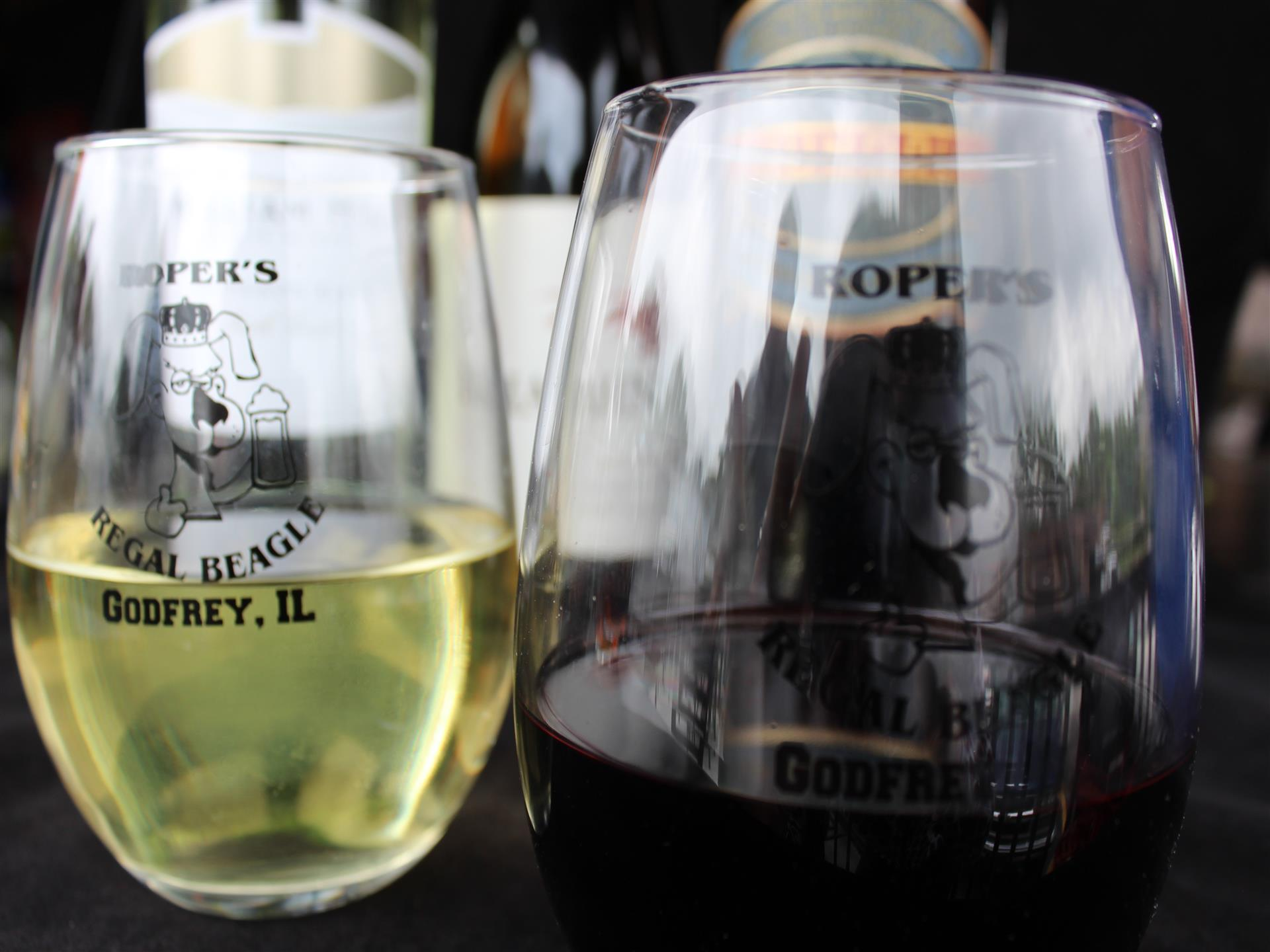 two glasses of red and white wine with Regal Beagle's logo printed on them.