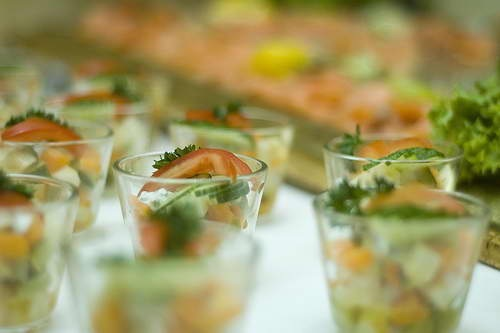 mini shot glasses filled with tomatoes, cucumbers and lettuce