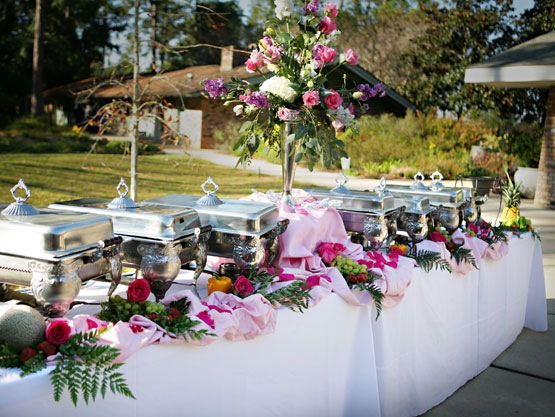 outdoor table setup for a buffet decorated with flowers