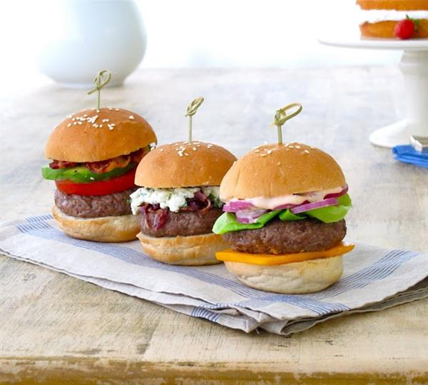three hamburger sliders with cheese, lettuce and tomatoes