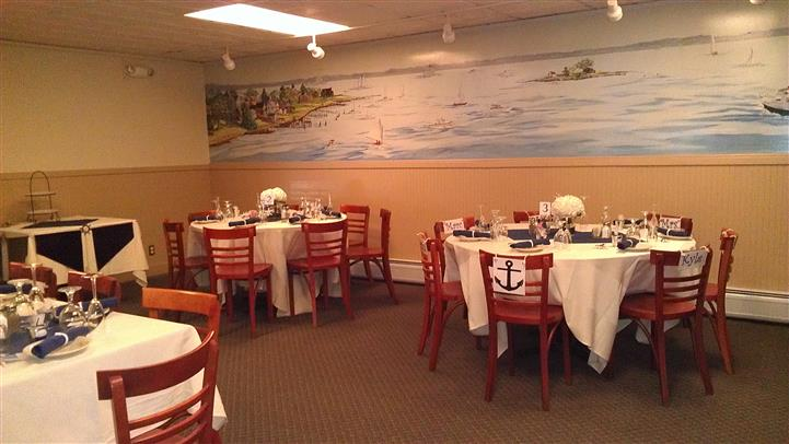 seating area with tables and chairs and a mural of of an ocean with boats painted on the wall