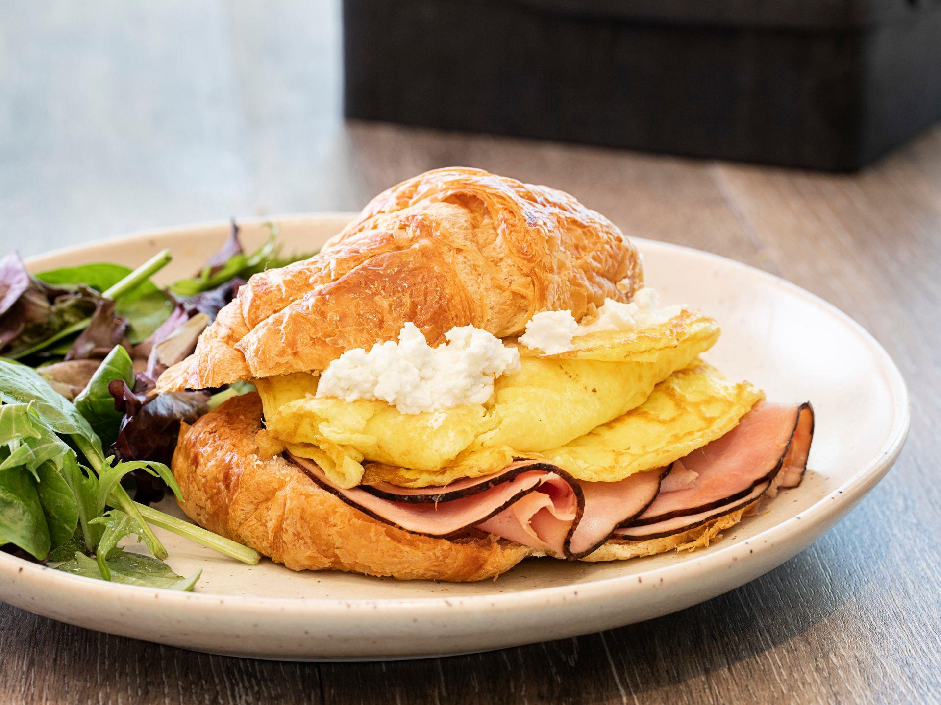 Ham, egg and cheese on a croissant with mixed greens